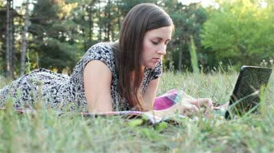 stock-footage-young-women-lying-on-grass-in-park-and-using-laptop
