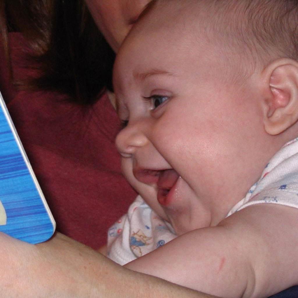 bebelus care se uita la o carte cu povesti (www.babytalk.org)