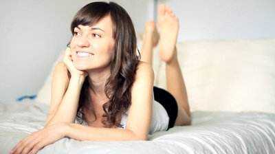 stock-footage-young-beautiful-happy-woman-lying-in-bed-flirting-with-camera